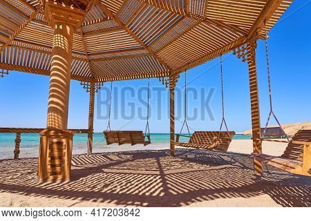 Swing Hanging From An Alcove On The Beach With Cozy Atmosphere Of Blue Sea And Blue Sky. Dreamy Para