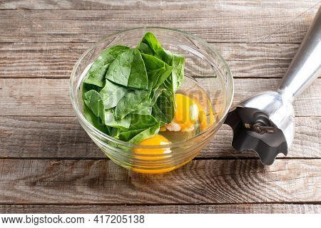 Eggs And Spinach In A Glass Bowl, Raw Ingredients For Cooking Healthy Spinach Pancakes On Wooden Tab