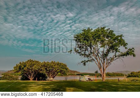 View Of A Camping Tent With Awning Pitched On The Dry Ground Under Beautiful Big Trees With Branches