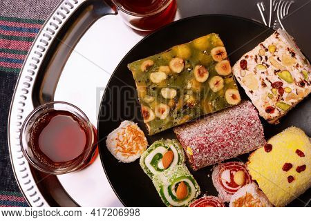 Top view of various traditional turkish delights with nuts and tea glasses