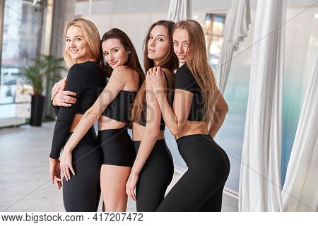 Group Of Female Before Fly Yoga Exercises In Fitness Training White Gym Loft Classroom. Intense Fitn