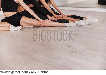 Female Athletes Stretching Legs And Exercising. Intense Fitness Training Workout In Loft Industrial