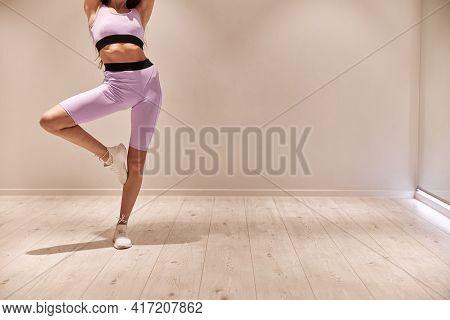 Female Athlete Stretching Legs And Exercising. Intense Fitness Training Workout In Loft Industrial G