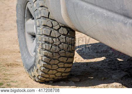 Muddy Off-road Tire With Rough Tread For 4x4 Four-wheel Drive Cars On Rural Clay Pavement Close-up.