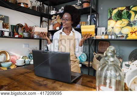 Smiling African Woman In White Shirt, Apron And Eyeglasses Sitting At Decor Shop And Holding Two Box
