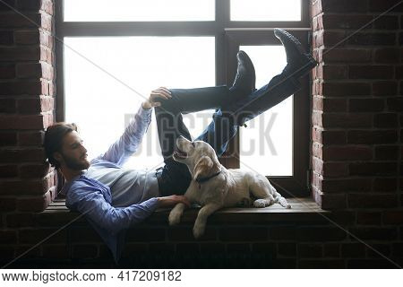 Full length portrait of a young man lie with his Golden Retriever dog on the windowsill in a loft-style room. A man and a pet.