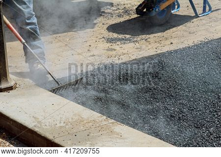 Man With A Special Tool Takes A Repair Asphalt Covering While Laying Asphalt New Road Surface