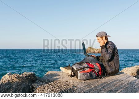 Digital Nomad Working With His Computer During A Trip. Person Celebrating A Triumph And Looking At H