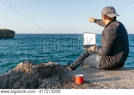 Traveler Man Using His Computer During His Trip Along The Coast And Pointing To A Plane That Crosses