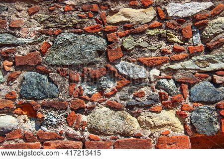 Wall Made Of Natural Rocks, Bricks And Scrap Bricks As A Background