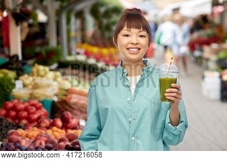 diet, healthy eating and detox concept - happy smiling young asian woman drinking green vegetable juice or smoothie from plastic cup with paper straw over street market background