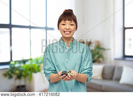 recycling, waste sorting and sustainability concept - smiling young asian woman holding alkaline batteries over home room background
