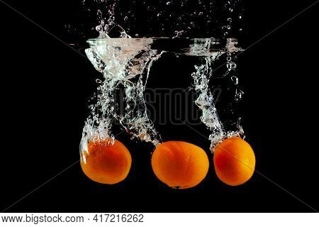 Three Fresh Tangerines Fell Into The Water With Splashes