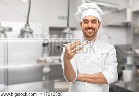 food cooking, asian cuisine and people concept - happy smiling male chef in toque holding something with chopsticks over restaurant kitchen background (focus on chopsticks)