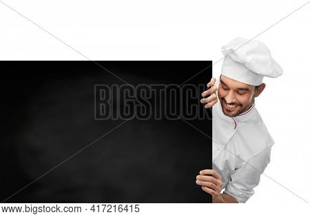 cooking, culinary and people concept - happy smiling male chef in toque with big black chalkboard white board over grey background