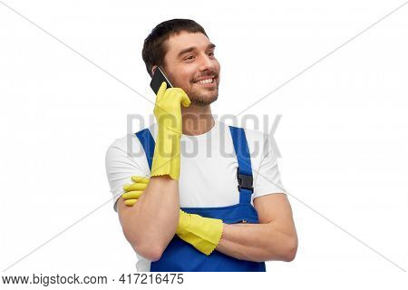 profession, cleaning service and people concept - happy smiling male worker or cleaner in overall and gloves calling on smartphone over white background