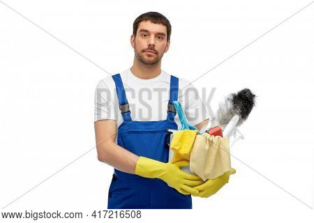 profession, service and people concept - male worker or cleaner in overall and gloves with cleaning supplies over white background