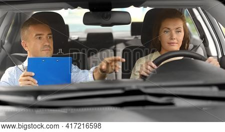 driver courses, exam and people concept - young woman and driving school instructor with clipboard in car