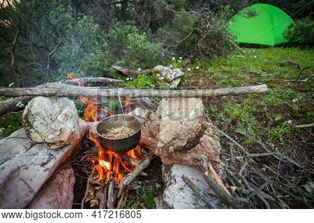 Touristic kettle on fire of burning campfire in camping in the hike. Cooking food in forest on wooden firewood.