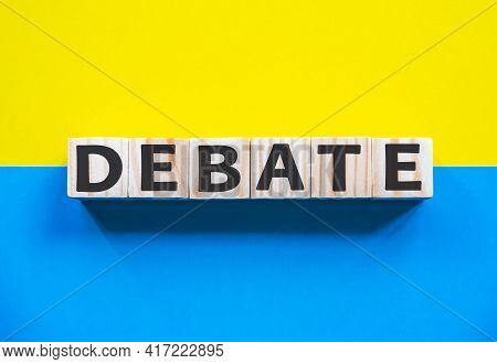 Word Debate On Wooden Cubes With Word On Beautiful Yellow And Blue Background. Business, Media Marke