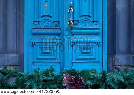 Ornate Door Handle With Old Double Wood Door Painted In Blue. Vintage Wooden Doorway And Defocused F