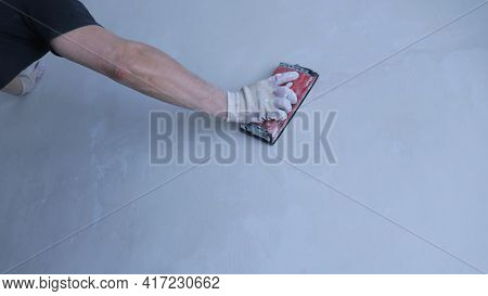 Sanding Machine In The Hand Of A Worker With The Force Of Pressing On The Surface Of The Wall During