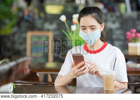 Asian Women Wear Medical Mask And Using Mobile Phone Sitting In Coffee Cafe , Women Wear Mask Preven