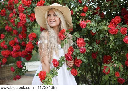 Cute Blonde In A Big Straw Hat On A Background Of Red Roses. Fashionable Outdoor Photo Of Gorgeous B