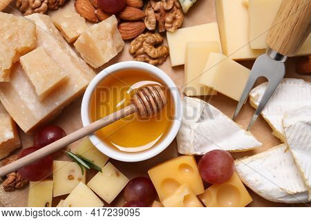 Cheese Plate With Honey, Grapes And Nuts On Wooden Board, Top View