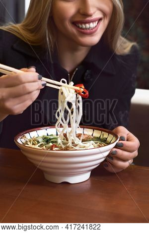 Female Hands Hold A Bowl With Asian Traditional Soup. Beef Pho Bo With Eggs.