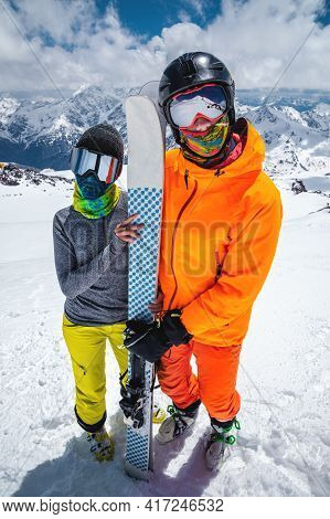Portrait Of A Pair Of Young Skiers Athletes Man And Woman In Ski Masks With Skis Stand And Look At T