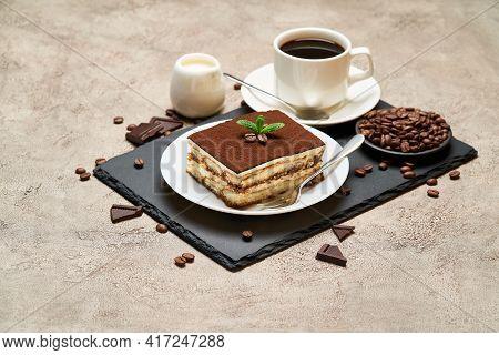 Portion Of Traditional Italian Tiramisu Dessert And Cup Of Espresso Coffee On Grey Concrete Backgrou