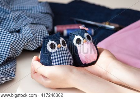 Child Holds In His Hands Hand Made Owls. Craft Tools And Materials On The Table.