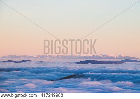 View Of The High Tatras In Slovakia, Which Rise Above The Clouds And Are Covered With Snow. View Fro