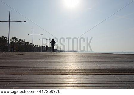 Thessaloniki, Greece - December 30, 2013 : People Walking On A Wooden Promenade Next To The Aegean S