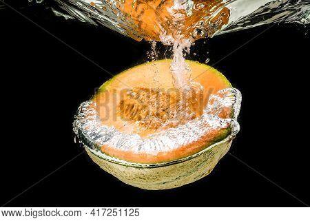 Half Of Orange Cantaloupe Melon Sinking, Isolated On Black