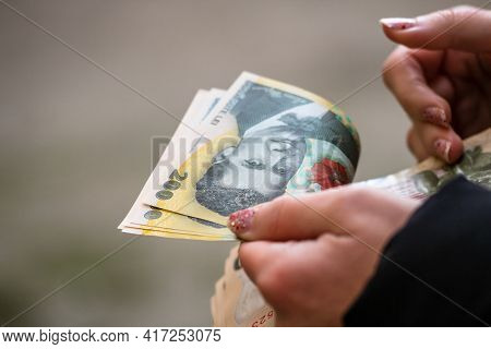 Selective Focus On Detail Of Lei Banknotes. Counting Or Giving Romanian Lei Banknotes. World Money C