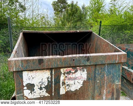Burke County, Ga Usa - 04 15 21: A Green Rusted Waste Dumpster At A County Dump Empty