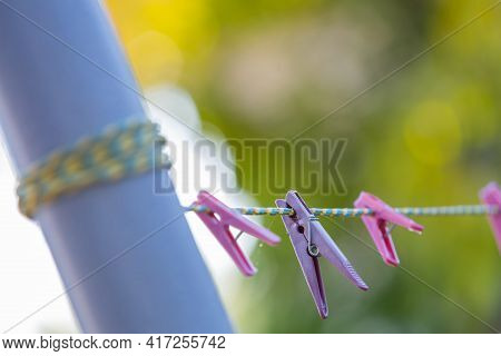Focus On A Blue Clothespin, Pink And Blue Clothespins Hanging On A Clothesline, Shallow Depth Of Fie
