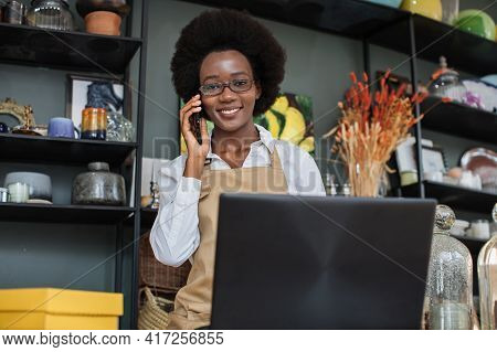 Close Up Of Pretty African Saleswoman Talking On Mobile And Typing On Laptop At Decor Shop. Various