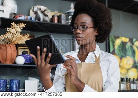 Charming African Woman In Eyeglasses And Beige Apron Working On Digital Tablet At Decor Shop. Pretty