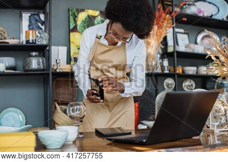 African Saleswoman In Eyeglasses Taking Picture Of All Assortment Of Decor Shop On Modern Smartphone