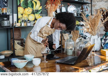 Pretty Black Woman In Apron Creating Online Catalogue Using Wireless Laptop. African Saleswoman In E