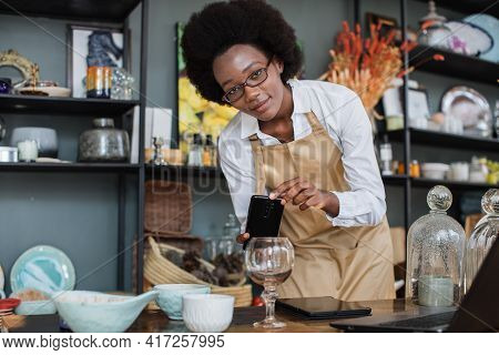 Close Up Of African Saleswoman In Eyeglasses Taking Picture Of Decorations And Glass In Shop On Mode