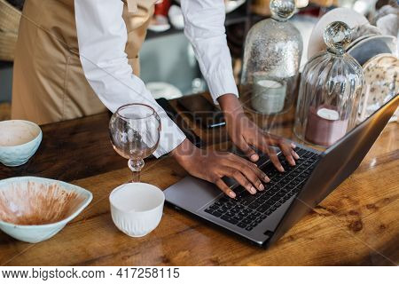 Close Up Of African Saleswoman In Beige Apron Using Laptop At Store During Receipt Of Goods. Beautif
