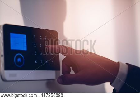 Mans Hand Enters Authorization Code Pin On Home Alarm Keypad.