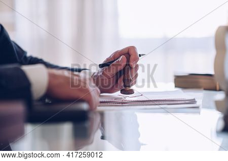 The Mans Hand Holds A Pen And A Notary Stamp.