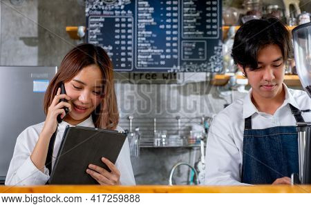 Barista Woman Or Coffee Maker Answer The Phone To Get Order From Customer While Her Co-worker Prepar
