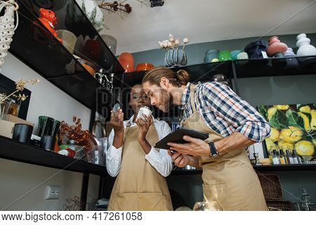 Handsome Caucasian Man With Digital Tablet In Hands Smelling Aroma Candle That Holding African Sales