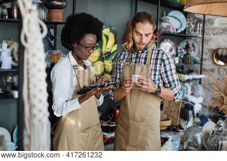 Beautiful Saleswoman Typing On Digital Tablet While Bearded Seller Holding Ceramic Cup. Two Multieth
